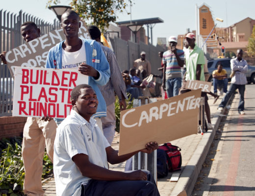 Johannesburg, South Africa - MAY 20: Laborers needing work hold signs with their specialities - electrician, plumber, carpenter - outside a hardware store in Fourways. They say they used to get several jobs a day, but now they are lucky to get one every two weeks. (Photo by Melanie Stetson Freeman/The Christian Science Monitor  via Getty Images)