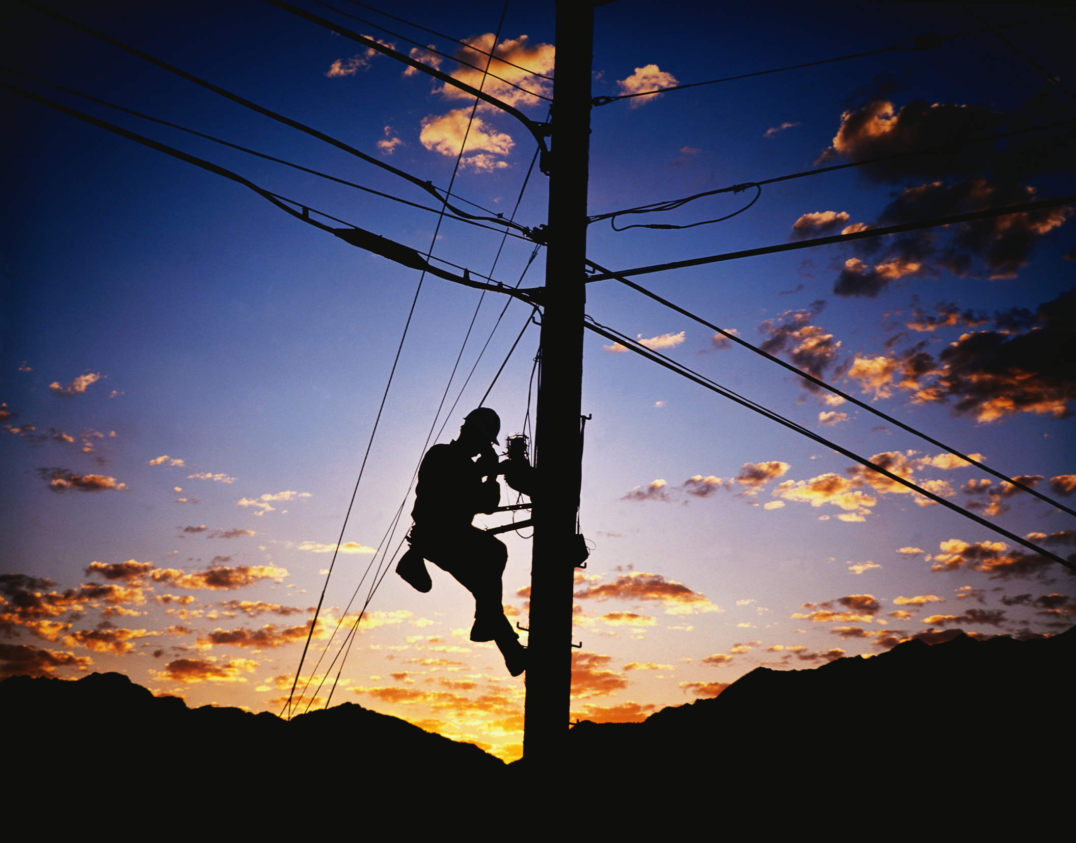 Silhouette of Lineman and Telephone Pole
