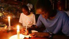 Fourteen-year-old Zimbabwean twins Gugulettu (L) and Ntokozo Ndebele read and write by candlelight at their family home in the capital Harare February 19, 2006. Frequent electricity failures and load shedding plague the country and are the result of ageing generating and distribution equipment and a critical shortage of foreign currency to import the necessary spare parts. Zimbabwe does not produce sufficient electricity for its own needs so it imports power from neighboring South Africa, Mozambique, Zambia and the Democratic Republic of Congo (DRC).  REUTERS/Howard Burditt