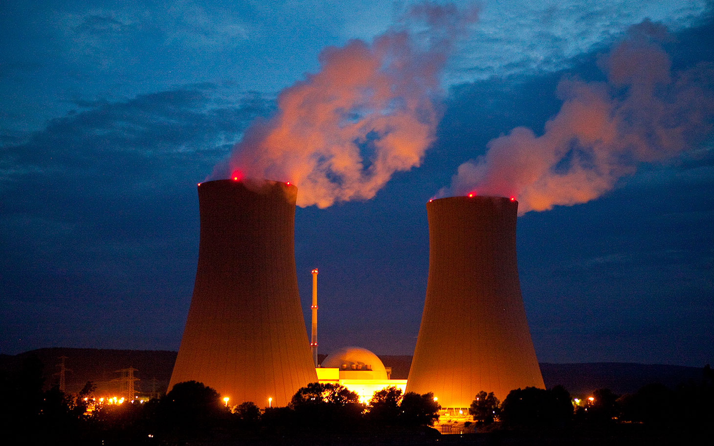 Cooling towers emit vapor into the night sky at a nuclear power plant operated by EON SE in Grohnde, Germany, on Wednesday, Aug. 07, 2013. Germany's air pollution is set to worsen for a second year, the first back-to-back increase since at least the 1980s, after Chancellor Angela Merkel's decision to shut nuclear plants led utilities to burn more coal. Photographer: Krisztian Bocsi/Bloomberg via Getty Images